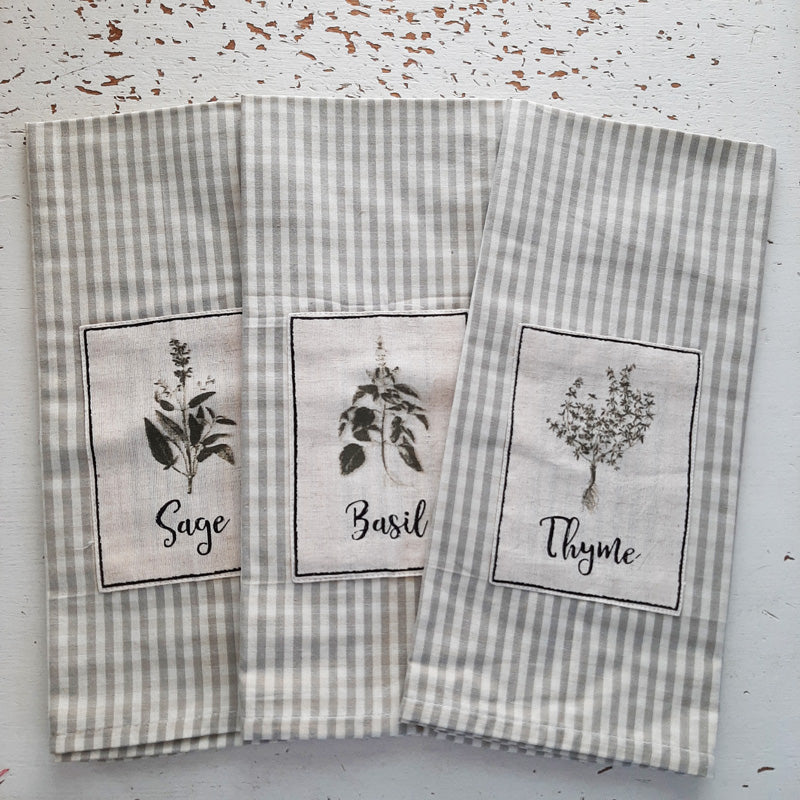"Our Herb Garden Dish Towels come in three designs: Sage, Basil, and Thyme . Each towel features a soft grey and cream striped pattern with a fabric patch depicting the image of a different garden herb. Measures 28"" high by 18"" wide and is 100% cotton. Set of three."