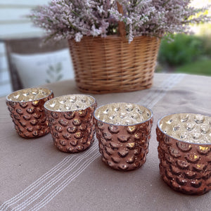 The Hobnail and Mercury Glass Votive Holder Set brings rustic elegance to any table setting. The aged amber design lends a vintage feel while the inside is a silver mercury glass. Together they create a soft glow. Set of four. Each is 3'' dia. x 3''H