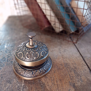 "The Hotel Desk Bell is a vintage style reproduction of the iconic bells found at front desks of general stores, hotels and post offices. This sturdy metal bell features a beautifully embossed design and an aged patina.  3.75"" Diam"