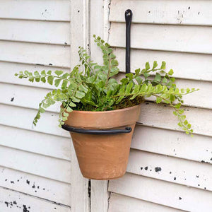 This Iron Wall Mounted Plant Hanger makes an eye-catching display for any patio, porch or room in your farmhouse.  Features a forged iron wall bracket with a terracotta pot. Let geraniums pop or grow your favorite herb. We like the idea of using one indoors to create a unique taper candle holder with a little moss tucked in.