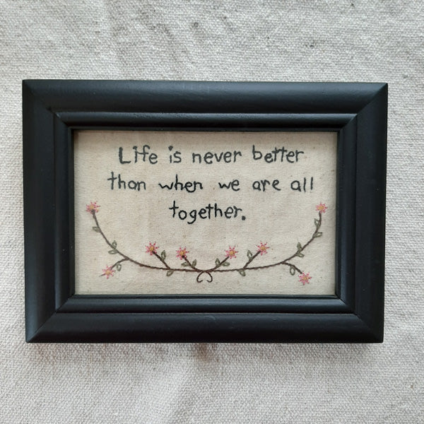 "Life Together Sampler is a primitive stitchery that features the phrase, ""Life is never better than when we are all together."" The bottom of the design is accented with a border of pretty pink flowers. Includes a black wooden frame with a glass front to protect the fabric stitchery. Hangs on a sawtooth hanger or can be converted and displayed tabletop. Measures 5"" high by 7"" wide."