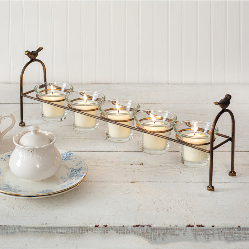 The Little Bird Votive Holder is perfect for long farm tables. The relaxed elegance of its design is just right for farmhouse style décor. It includes five glass votive holders in an aged brass finish frame with little birds perched on each end. This sweet candle holder is infused with quaint cottage style to add warmth to any room. The glasses each measure 3½'' dia x 3''H. This item is shown with votive candles, not included. 20''W x 3½''D x 7¼''H