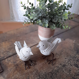 "This Little Birdie Figurine Set adds a sweet touch to shelves and tabletops. The set of two features charming little metal birds with an antique white finish. Let these two birds brighten your day as you find them tucked away or on display. Each approximately 2""H"