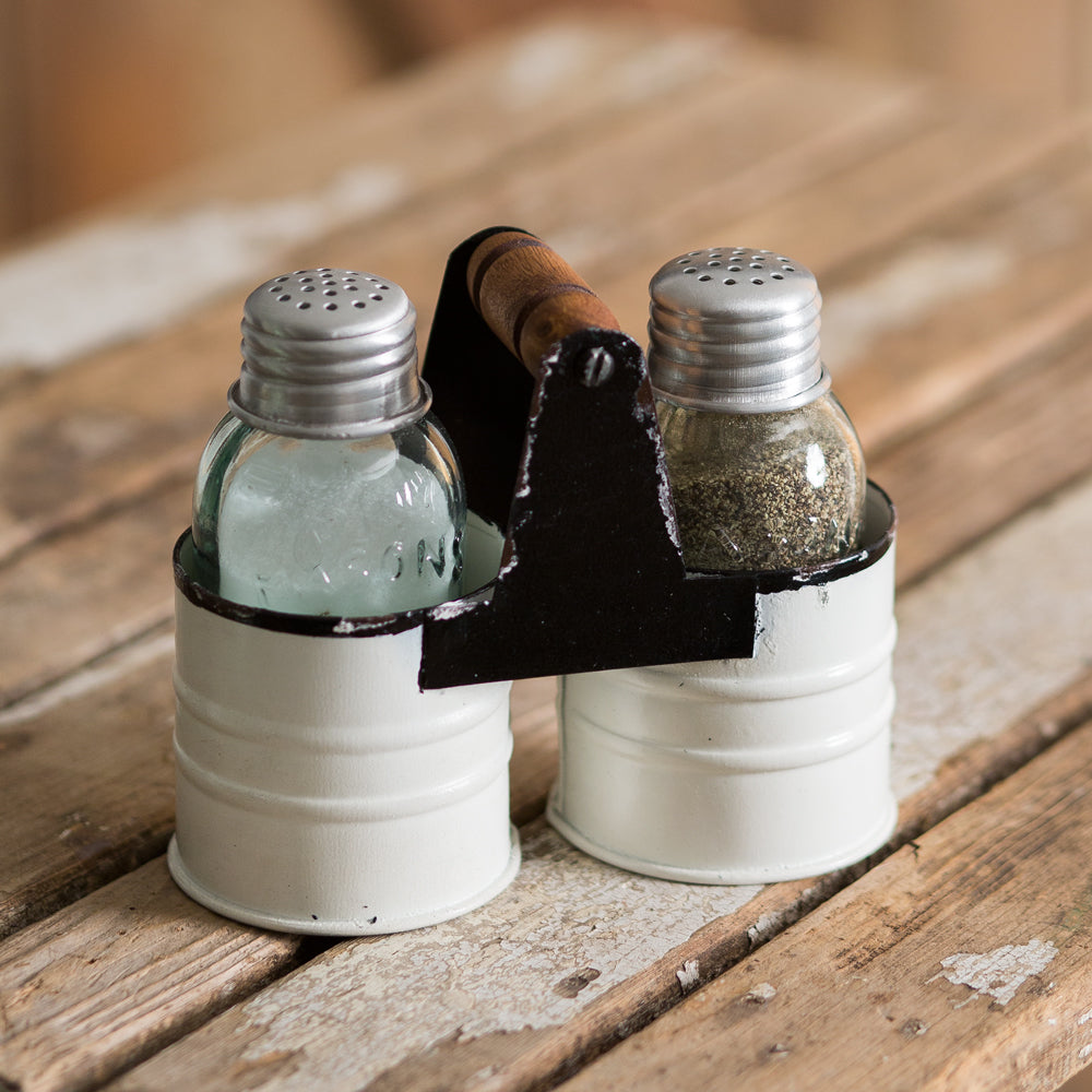 This Mason Jar Salt and Pepper Caddy adds a sweet, vintage farmhouse feel to your kitchen. Features mini glass mason jars to hold salt, pepper with metal lids. The antique white enamel style caddy has a time-worn feel, with a wood handle .