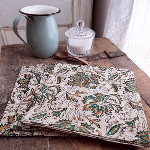 The Mediterranean Farmhouse Napkins feature an intricate floral pattern in down-to-earth green, mustard, and black hues. The handcrafted print floral offers a rustic charm with a vintage feel that evokes an old-world farm table on a warm terrace surrounded by vines and greenery. 100% cotton. Set of four. 20 x 20