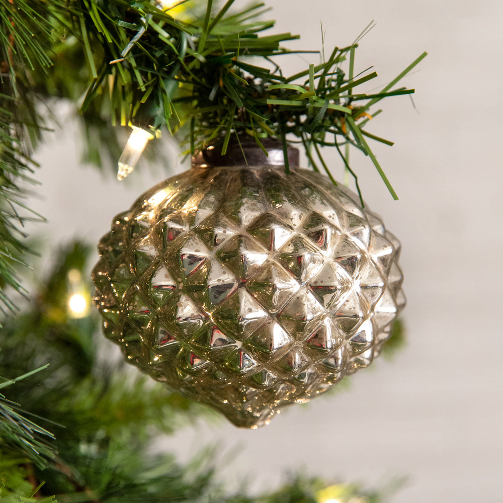 There's something special about the way the light catches this Mercury Glass Diamond Ornament. Inspired by vintage ornaments, the aged mirrored glass and diamond pattern will sparkle all over your Christmas tree.  These handcrafted ornaments are hand blown into molds to create a quality thick glass ornament in the same style as years past. This ornament comes with a gold tie.