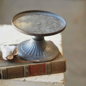 Showcase candles by adding height and elegance with our Monterey Candle Holder Pedestal. This antique style pillar candle holder features an aged pewter look with a refined ribbed detail along the base.
