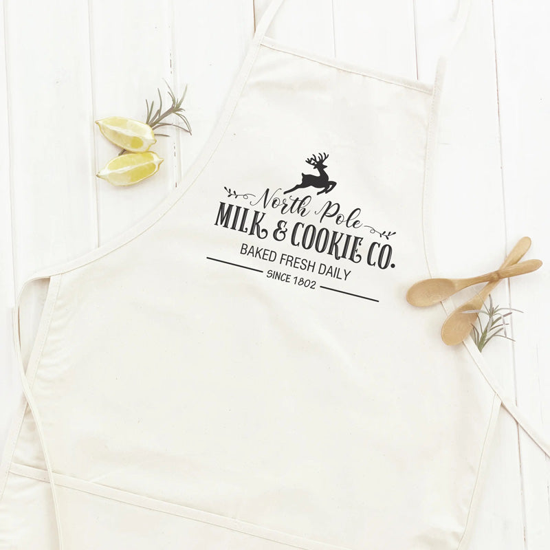 Get down to Christmas cooking in style with this North Pole Cookies and Milk Co Apron.  Custom designed and handcrafted in the USA from the highest quality materials, this apron adds a little whimsy to your farmhouse kitchen.  The comfortable cotton canvas fabric features beautiful lettering. Made in the USA