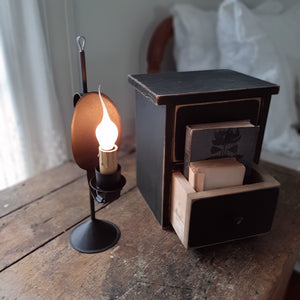 Our Old Salem Reflector Lamp hearkens back Colonial times when many tasks were accomplished by candlelight. This candle lamp captures that old-timey feel with the modern convenience of electricity. Made with a black metal finish, this small light features a beautiful design, which includes a reflector back and a faux candle.