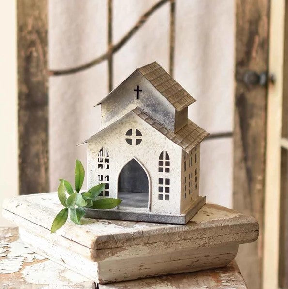 "This Old Tin Chapel makes a sweet addition to any tabletop or shelf. With weathered white paint and simplicity of detail, it offers a quiet charm. Add a tealight candle to create a magical glow from the windows and cross. 7""L x 7""W x 9""H"
