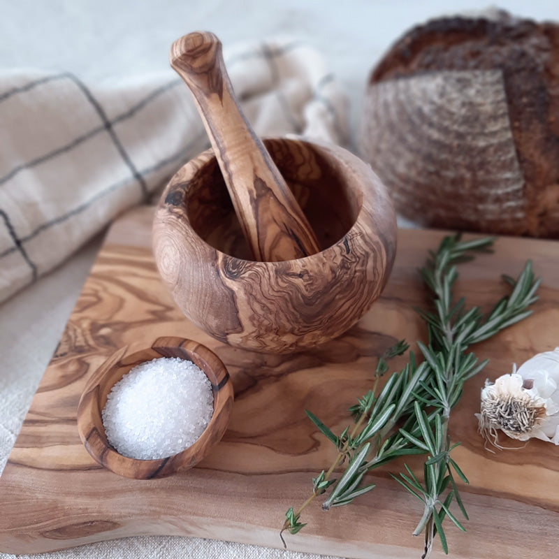 "Add this rustic kitchen helper to your lineup of farmhouse cooking utensils. Made by hand, our Olive Wood Mortar and Pestle is ideal for crushing herbs and spices. The olive wood is an extremely hard surface that can sustain the force of grinding and mashing. CARE INSTRUCTIONS: Hand wash and polish with food safe oil. 3"" diam"