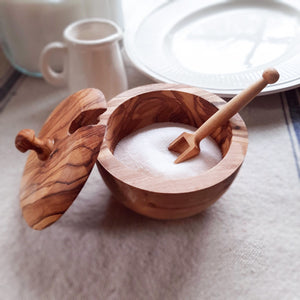 Made by hand, our Olive Wood This Sugar Bowl is suitable for storing sugar, salt and spices. The removable lid allows for easy refilling. The scoop is included. The beautiful grain of the olive wood lends and earthy, rustic touch to your farmhouse kitchen. Olive wood is a hard wood making it very dense and durable for everyday use.
