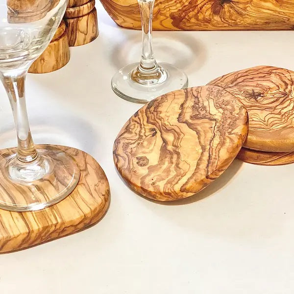 "This set of Olive Wood Coasters is the perfect holder for your favorite beverage. All natural, these lend a rustic touch with down-to-earth elegance. Each coaster is made from a single piece of olive wood and no two pieces are alike. Olive wood is a hard wood making it very dense and durable for everyday use. Olive wood is nonporous so no germs or odors are retained. CARE INSTRUCTIONS: Hand wash and polish with food safe oil. Set of four, each approximately 4"" in diameter"