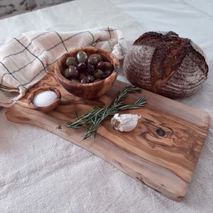 Add old-world charm to your farm kitchen with our Rustic Olive Wood Cutting Board.  Perfect for cutting bread, slicing cheese, chopping vegetables and carving meat. Makes an ideal charcuterie board for small gatherings. The olive wood grains lend a natural beauty. Each board is one solid plank, which eliminates future warping and cracking. One edge features a natural cut. Olive wood is a hard wood making it very dense and durable for everyday use. Olive wood is nonporous so no germs or odors are retained.