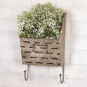 I can see this Aged Metal Wall Basket with Hooks packed with pine greens or dried hydrangeas. It also makes a great little mail caddy and key holder for a farmhouse entryway. Features a perforated front, which is inspired by vintage olive buckets, two hooks and a weathered finish to give it a timeworn feel.