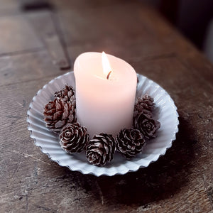 "The Enamel Fluted Mini Pie Pan Candle Holder features a durable white enamel finish with an old primitive feel. Inspired by antique fluted pie pans, this taper candle holder fits right in with farmhouse style decor. (Candle and pine cones not included) 5"" D x .75""H"