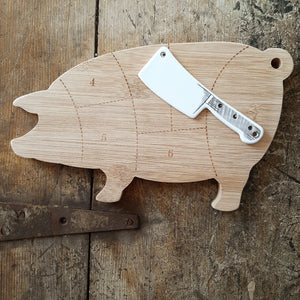 "Our Pig Cheeseboard Gift Set is a farmhouse entertaining must-have. Use as a cheese and charcuterie board and display your meat and cheese pairings. Shaped like a pig, the cheeseboard features a butcher chart and comes with a coordinating white ceramic spreader shaped like a miniature cleaver. Cheeseboard measures 10.23""""w x 6.18""""h x 0.59""""d; spreader measures 4.72""""w x 1.41""""h x 0.11""""d Cheeseboard and spreader are hand wash only"