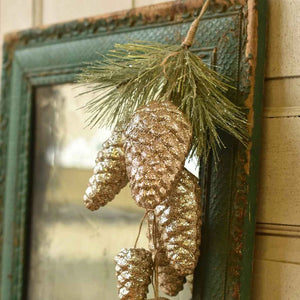 "Elegance and sparkle come together in this eye-catching Gleaming Pine Cone Drop. Features seven golden pine cones cascading down a twine rope with a hint of glittery pine at the top. Display on a door, add sparkle to a wreath or decorate your mantle. 20""H"