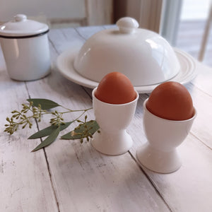 "Our Porcelain Egg Cups add a touch of elegance to your breakfast table. The egg cup is the perfect serving solution for soft- or hard-boiled eggs. Egg servers hold eggs upright so you can snip off tops and enjoy. With their neat style and simple lines, these porcelain egg cups not only serve as a necessary dining tool but as a true table decoration as well! Made of elegant white porcelain, dishwasher safe for easy cleaning. Set if two.  2"" Diam x 2.5""H"