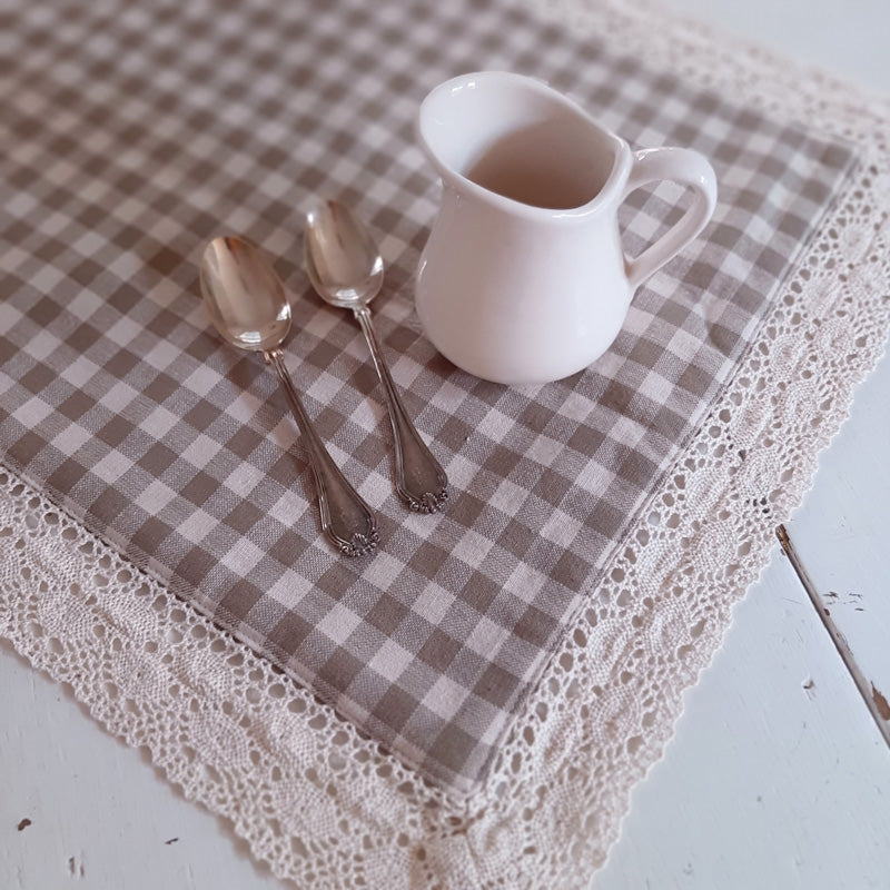 "The combination of oat and cream checks with a lacey crochet trim lends an easy farmhouse charm to these placemats. Our double-sided Oat and Cream Prairie Placemats combine the natural clay color of linen with a bright creamy background for rustic elegant style. Classic tailoring with crochet edging, these placemats are perfect for dressing up your farmhouse table. Gingham checks offer country charm while the lace edging adds a vintage touch.  100% cotton. Dry clean. Set of 2 Placemats 14"" x 18"""