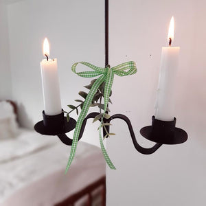 This rustic candle holder looks like it was hand forged at an old blacksmith shop from the 1800s. The simplicity of its design gives it casual elegance that suits farmhouse living. The graceful twist along its base gives it added elegance. The Primitive Double Taper Candle Holder is metal and has a black finish. We've added a sprig of greenery along with a ribbon for extra charm. Also, looks beautiful with our Forest Pine Candle Rings. Holds regular two taper candle.