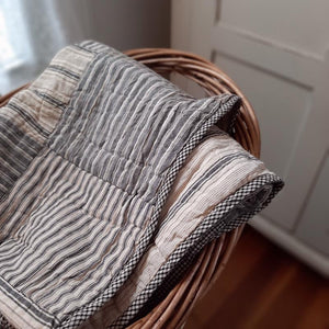 "Add a cozy, vintage farmhouse feel to your living room or reading nook with this quilted throw. Our Prairie Patch Quilted Throw is made of 100% cotton. It features blocks of fabric in various country patterns in a warm tan and gray color scheme. The back has a simple ticking stripe style pattern. 50""W x 60""H"