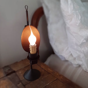 Our Old Salem Reflector Lamp hearkens back Colonial times when many tasks were accomplished by candlelight. This candle lamp captures that old-timey feel with the modern convenience of electricity (Thank you, Mr. Edison). Made with a black metal finish, this small light features a beautiful design, which includes a reflector back and a faux candle.