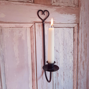 "The Rustic Heart Taper Candle Holder adds primitive farmhouse charm to any room. The relaxed design features a metal taper holder with an aged, black/gray finish. The top of the holder features a beautiful heart shape and a pre-drilled hole for hanging. The holder curves up at the base and holds a candle tray with a taper candle cup. Measures 12"" high by 2"" wide with a ⅞"" candle cup."