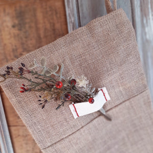 "Our classic Rustic Heirloom Burlap Stocking will make a beautiful statement on your mantle for years to come. Generous in size for packing in special treasures with a signature heirloom tag and simple red stitching. Stocking toe is left facing. 100% Burlap. 23""H (Includes one stocking.)"