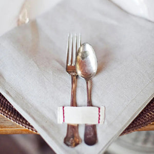 Farmhouse elegance is made easy with these Rustic Heirloomed Linen Napkins.  The set of four 100% linen napkins is made with a warm, earthy neutral linen with a signature tag detail with simple red stitching. The napkins come packaged in kraft bags nostalgic of a rustic market bakery and tied with a single waxed thread cord. Each of the Rustic Heirloomed Linen pieces is inspired by vintage details and craftsmanship. They are meant to be used, loved and passed down through the generations. This collection is