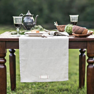 Give your farm table a vintage, old-world feel with this Rustic Heirloomed Linen Table Runner.  Made with 100% linen, the runner is a warm, earthy neutral tone and features a signature tag detail with simple red stitching. The Rustic Heirloomed Linen Table Runner comes packaged in a kraft bag nostalgic of a rustic market bakery and tied with a single waxed thread cord. Each of the Rustic Heirloomed Linen pieces is inspired by vintage details and craftsmanship.