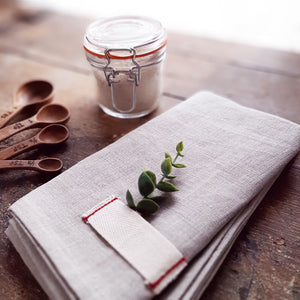 Give your farm table a vintage, old-world feel with this Rustic Heirloomed Linen Table Runner.  Made with 100% linen, the runner is a warm, earthy neutral tone and features a signature tag detail with simple red stitching.