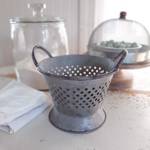 "Made of galvanized metal, our Rustic Tin Colander is a decorative colander with a weathered, distressed finish. It has a widened base, a repeating hole pattern, and a pair of carrying handles. Create the perfect centerpiece for your farm table or add to any kitchen shelf for instant charm. This Rustic Tin Colander makes the ideal display for dried flowers, potpourri, decorative eggs, or an endless list of other items.  8 x 6""H"