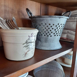 "Made of galvanized metal, our Rustic Tin Colander is a decorative colander with a weathered, distressed finish. It has a widened base, a repeating hole pattern, and a pair of carrying handles. Create the perfect centerpiece for your farm table or add to any kitchen shelf for instant charm. This Rustic Tin Colander makes the ideal display for dried flowers, potpourri, decorative eggs, or an endless list of other items!  8"" w x 6"" h"