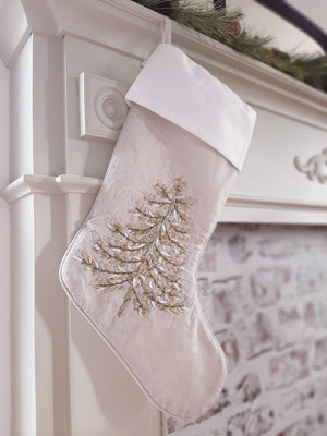 Accent your holiday decorations with our hand-crafted Ribbon Art Stocking with Tree. Featuring an array of intricate ribbon branches forming a classic evergreen tree that's decorated with beads for extra cheer. This stocking, and its unique texture, will become a centerpiece of your Christmas decor. Finished with a coordinating piped edge and a winter white cuff. The light oatmeal stocking has a hint of sparkle.