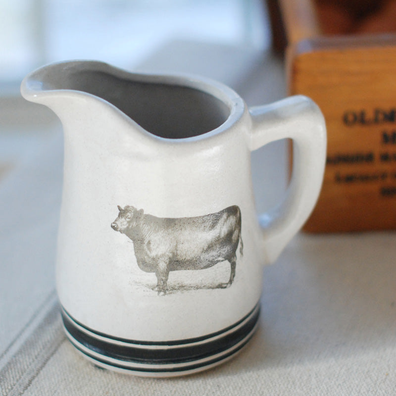 "This primitive Stoneware Cow Pitcher makes a great addition to a farmhouse kitchen. The bold black stripe and cow graphic against the oatmeal stoneware lend a vintage quality that is in keeping with farmhouse style decor. 6.5"" x 5.5""H"