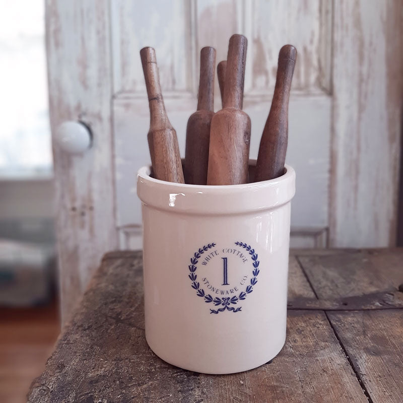 "This handsome Stoneware Crock is inspired by early 20th century pottery found in farmhouses throughout the US. This reproduction crock has an oatmeal color with a blue White Cottage Stoneware Co. logo, making this piece a perfect accent for American farmhouse style kitchens. Use to store cooking utensils or display your favorite flowers. (Rolling Pins and Flowers not included) 5.75"" Diam x 7""H"