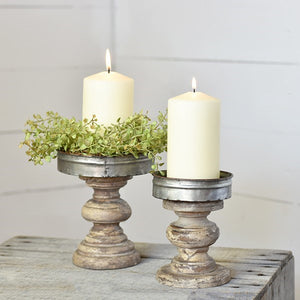 "With a beautiful turned wood base and a galvanized tin top, this set of two candle holders bring a warm, rustic feel to your mantle, table or dresser. Our Tin and Wood Pillar Candle Holder, Set of two creates farmhouse style and ambiance in any room. It accommodates one 4"" W pillar candle."