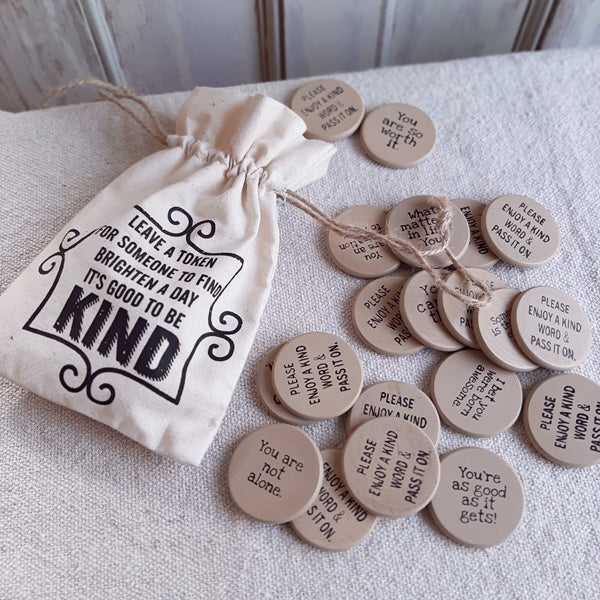 "Spread the love with our Tokens of Appreciation Drawstring Bag! A 5"" high by 4"" wide fabric bag is filled with 20 wooden tokens with positive phrases printed on them. Each token has an inspirational phrase, such as ""You can do this!"" and ""Be good to yourself. You deserve it!"" The drawstring bag is printed with the following instructions on the front: ""Leave a token for someone to find. Brighten a day, it's good to be kind."" Each token is approximately 1¼"" in diameter."