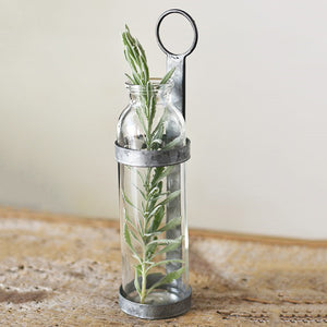 This unique vase can be hung on a wall or used on a tabletop. The beautiful vintage apothecary style glass jar is encased in a rustic tin holder, adding an industrial design quality. The Vintage Apothecary Wall Vase is a great way to display your favorite flowers.