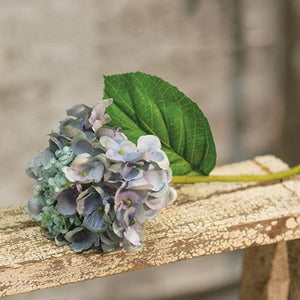 "Our Vintage  Blue Hydrangea Pick is a sweet summer floral made of faded blue fabric petals with hints of green on a green plastic stem. It has a large faux leaf jutting from the stem and looks charming as is or combined into a floral arrangement. It easily fits into baskets, buckets, and milk cans and more. 9"" high by approx 5.5"" wide by 5.5"" deep."