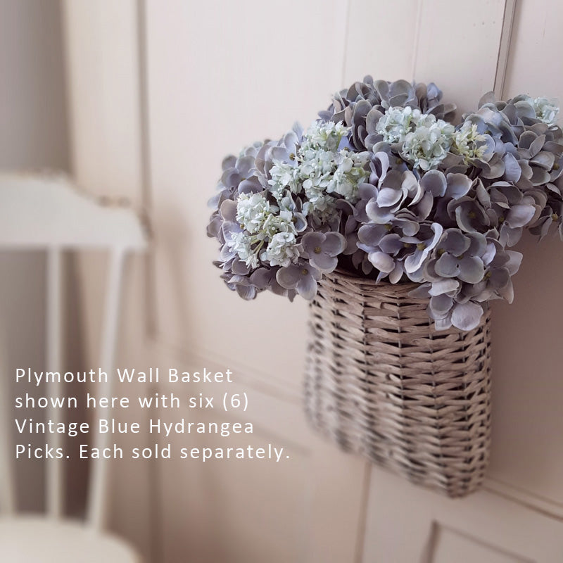 "Our Vintage  Blue Hydrangea Pick is a sweet summer floral made of faded blue fabric petals with hints of green on a green plastic stem. It has a large faux leaf jutting from the stem and looks charming as is or combined into a floral arrangement. It easily fits into baskets, buckets, and milk cans and more. 9"" high by approx 5.5"" wide by 5.5"" deep. Shown here with six picks."