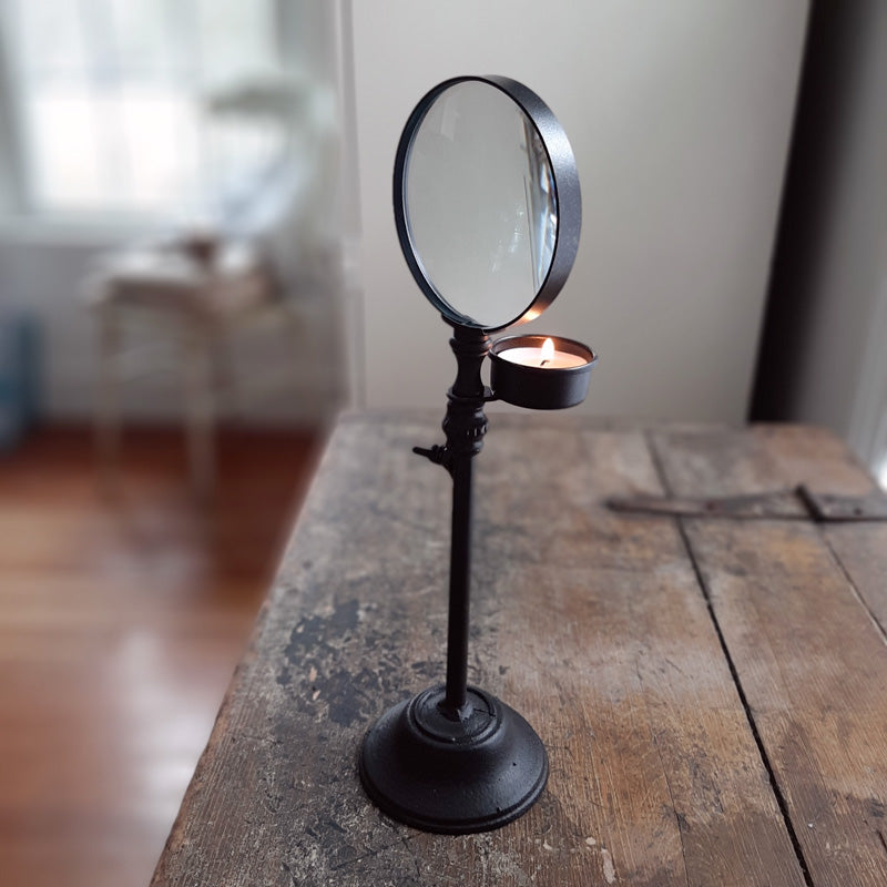 "This piece adds instant character to any room. The Vintage Industrial Magnifying Candle Holder features a dark brown/black matte finish with a large circular magnifying glass to enhance the candle's glow. This old-fashioned charmer burns one tea light candle (not included) and has a telescoping feature that allows it to extend to 17"" in height. The tea light holder cup is also adjustable to suit your needs. It makes a handsome addition to any home office, library or bedside table"