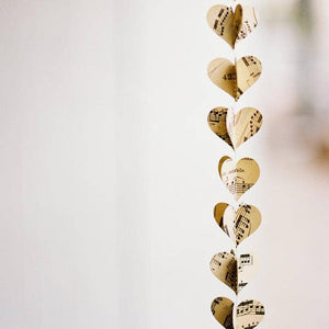 "This Vintage Sheet Music Paper Heart Garland makes a sweet accent for just about any room. This extra-long garland adds a special touch to rustic wedding décor or a vintage style bridal shower, and so much more. It is a great example of the recycle, reuse, repurpose movement. Each 60"" long garland is made of 80 hearts doubled up and machine stitched together so they can be folded back to create 40 3D shapes. Each heart measures 1.5"" H x 2"" W. Made in USA"