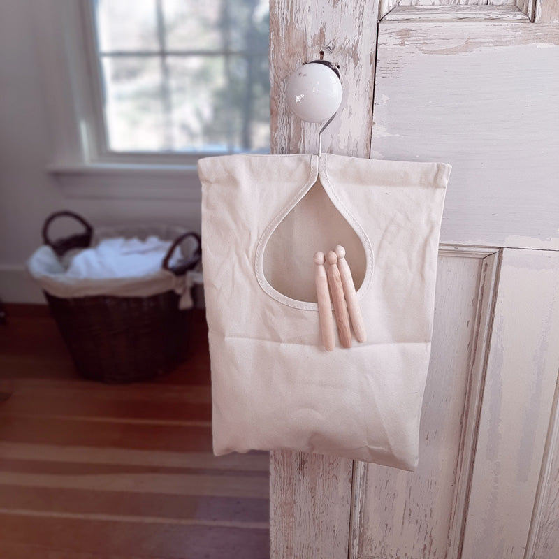 "Bring a little vintage flare to your laundry day. There's nothing better than fresh, crisp laundry off the line. Keep this sturdy natural colored canvas Vintage Style Clothes Pin Bag near at hand and never have to fumble for a clothes pin again. Features a durable, washable, water-repellent canvas bag that can hold up to 100 clothespins, a swivel hook for effortless hanging, and reinforced stitching around the opening for extra durability. 11""W x 15""H"