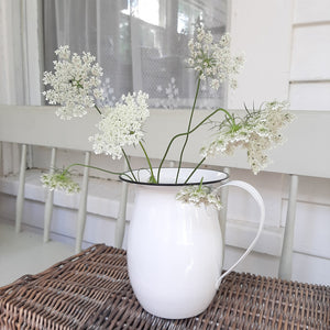 "Bring the easy charm of country cottage living to your farmhouse with our Vintage Style Enamel Pitcher with Black Rim. The simple allure of enamelware fits right in with any decor, but every farmhouse needs at least one piece. Inspired by flea market finds, our white enamel pitcher has black trim and makes the perfect vase for your favorite bouquet. Not food safe. Pitcher measures 6¼"" high by 5¼"" diameter (7"" wide with handle)."