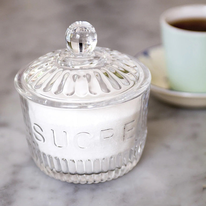 "This Vintage Style French Sugar Jar features Depression style glass, which evokes the textures, weight and aesthetic of Depression glass pieces popularly produced around the 1930's in North America. Inspired by creativity despite minimal resources, Depression glass was manufactured to be practical, beautiful and accessible.  This clear glass lidded sugar jar. Round jar with lid featuring ribbed edging, fluted accents and raised text details reading ""sucre"" (sugar in French). Adds a vintage touch to the brea"