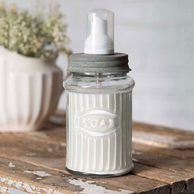 "This Vintage Style Foaming Soap Dispenser combines antique farmhouse style with a modern-day twist. The retro glass soap jar features an aged metal lid and white pump. Foaming soap dispensers help you save on regular liquid soap, too!  You can use foaming soap or any regular liquid soap.  For regular liquid soap just mix one part soap with three parts water, shake it up, and voila! Makes an adorable addition to any farmhouse kitchen or bath. 3.25""D x 7.5""H"