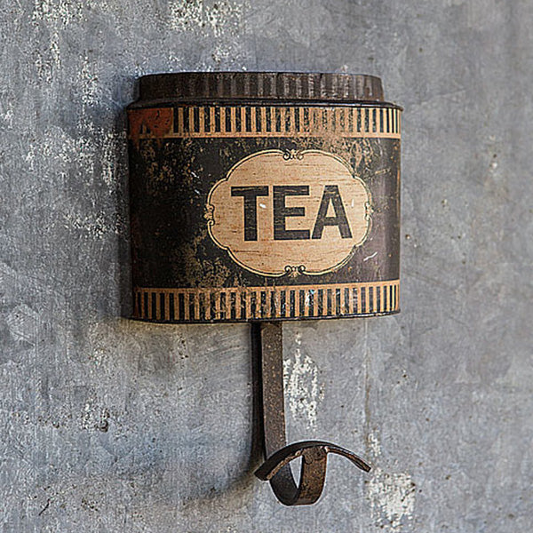 "Like something you'd find in an old English farmhouse, our Tea Canister Hook offers tons of vintage charm. Inspired by old tea boxes found at flea markets, this black tea canister, with its aged patina, includes an iron hook to hang your apron or dish towels. 5.25""L x 7.6""H"