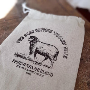 "Our Vintage Woolen Mills Mini Flour Sack is a drawstring fabric bag that features a sheep design and displays the words, ""The Olde Suffolk Woolen Mills. Spring Thyme Blend. This makes a unique gift bag for small treasures, or use to stash away clothespins in a vintage style laundry room. Hand washed wool."" 6.75""W x 9.25"" H"